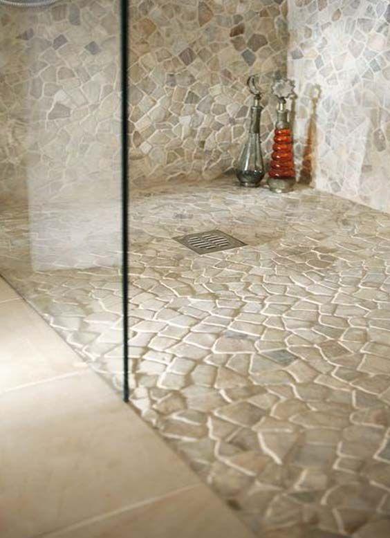white pebbles on bathroom floor, glass divider, floor tiles