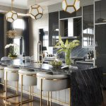 White Pendants With Geometric Shape With Golden Lines, Black Marble Island, Grey Cushioned Golden Legged Stools, Dark Grey Glossy Cabinet