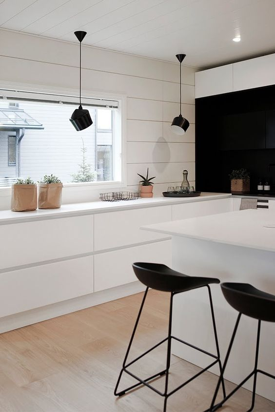 white thin topped kitchen island, black modern bar stools, white cabinet, white wood planks wall, white ceiling, black pendant, black wall