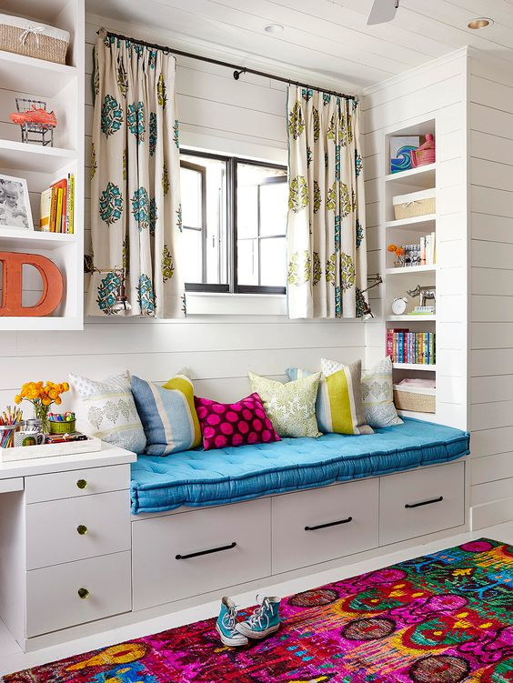 window nook, white floor, white wooden planks wall, wooden bench with drawers, blue cushion, shelves built in inside, windows, patterned curtain, floating shelves