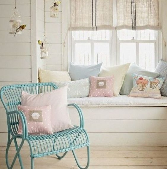 window nook, white wooden floor, white wooden bench, white cushions, pillows, off white shade on windows, green rattan chair