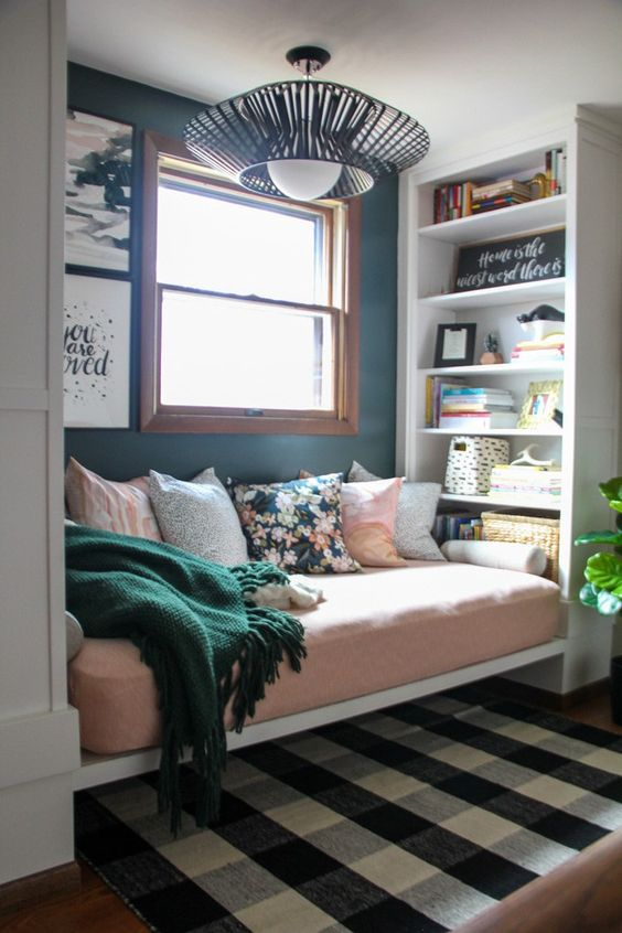 window nook, wooden floor, black white plaids rug, white shelves, white bench, pink cushion, pillows, green wall, pendants