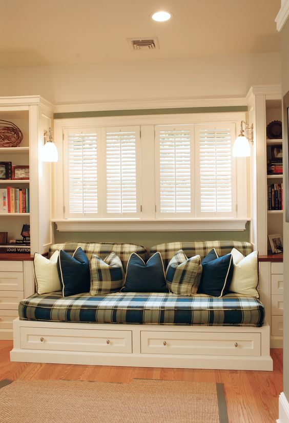 window nook, wooden floor, white bench, plaid cushion, sage green wall, white shelves and drawers, sconces, drawers under the bench