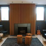 Woden Slats On The Accent Wall With Fireplace, Wooden Floor, Dark Grey Rug, Woocen Block Coffee Tables, Black Leather Sofa, Black Leather Chair, Dark Grey Wall