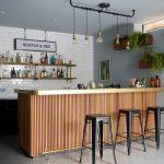 Wooden Bar Island, Beige Flooring Tiles, Grey Wall, White Subways Tiles, Floating Shelves, Glass Bulb Penadants, Black Stools