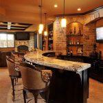 Wooden Bar Island With Marble Top, Brown Leather Stools, Beige Floors, Orange Pendants, Open Bricks Wall