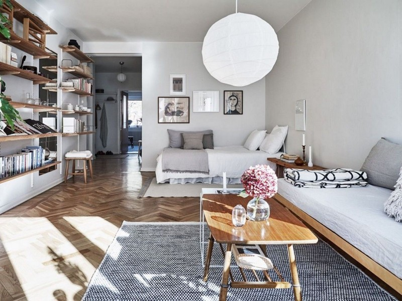 wooden chevron floor, rug, wooden bench with white bed, white bed, white wall, white lantern pendants, floating shelves along the wall