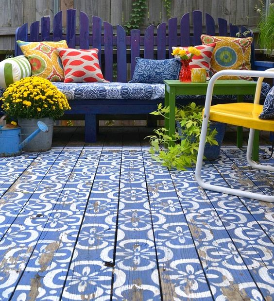 wooden deck with blue white bohemian style, purple wooden bench, blue cushion, colorful pillows, yellow metallis chair, flowers, plants