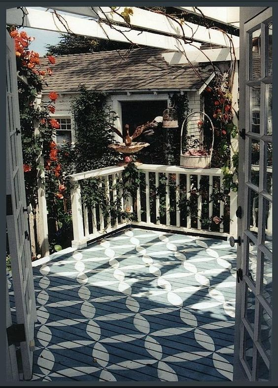 wooden deck with blue white painted pattern, white fences, vines, white wooden pergola ceiling
