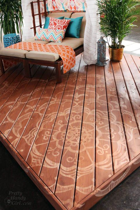 wooden deck with subtle stenciled pattern, double lounge chairs with beige cushions, colorful pillows, shade, plants, side table