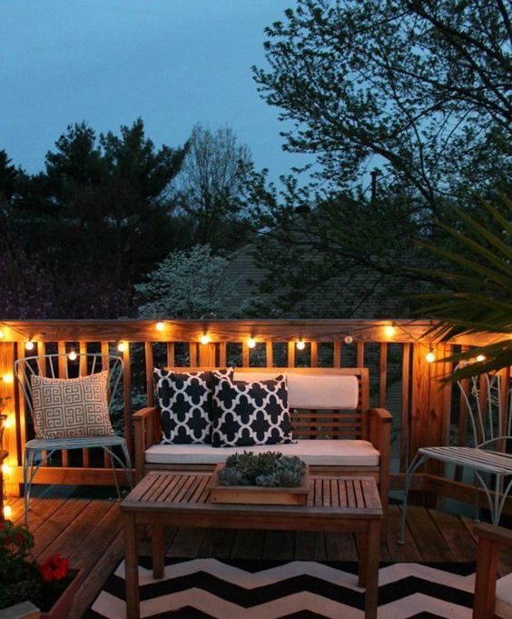 wooden deck, wooden bench, wooden table, white chairs, wooden fence, fairy lights