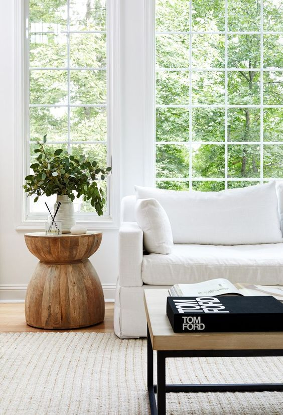 wooden end table shaped like an hourglass, wooden floor, rug, white sofa, glass window
