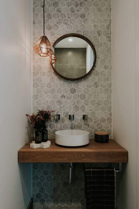 wooden floating vanity, towel holder under, white round sink, off white hexagonal wall tiles, round mirror, prism pendant