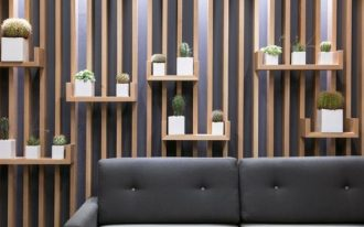 wooden slats accent on the living room's wall, with small floating shelves with plants on the pot, grey flooring, grey sofa