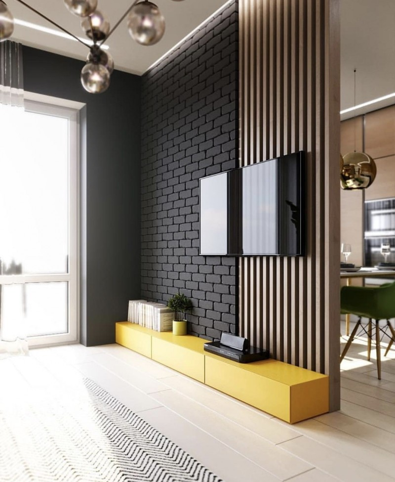 wooden slats on the wall partition beside black open brick wall, low yellow cabinet, wooden floor, modern pendants