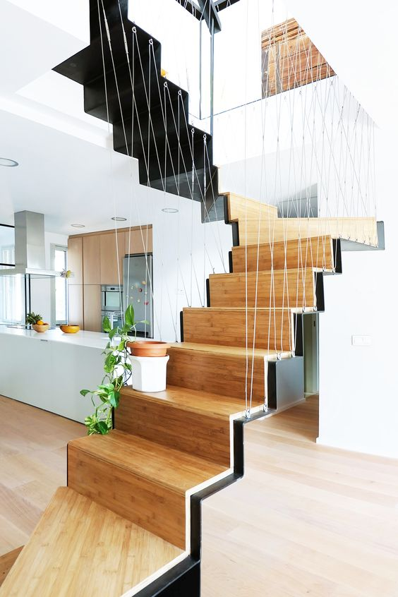 wooden stairs with black metal staris support, wire railing, wooden floor, white wall, kitchen