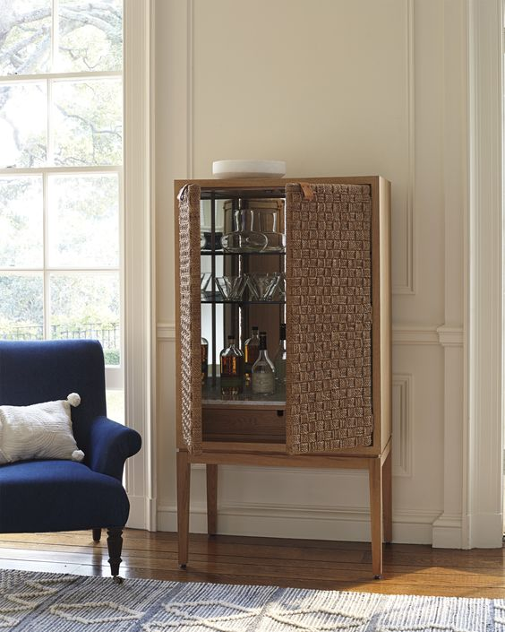 woven cabinet for wine, living room, wooden floor, white wall, blue chair, white pillow