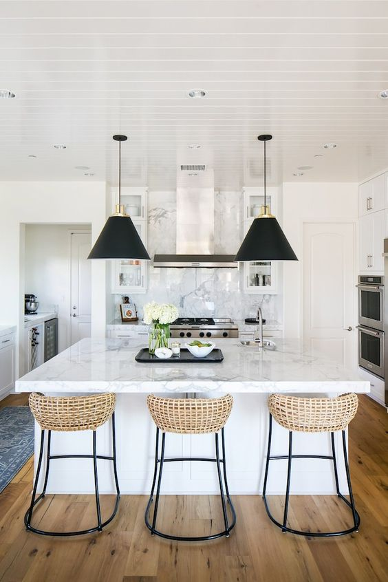 woven rattan back bar stool with black metal legs, white marble top, white wooden ceiling, white wall, white marble backsplash, black cover pendants
