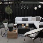 Backyard Corner, Grey Floor Tiles, Black Rattan Coffee Table, Black Rattan Corner Sofa With White Cushion, Black Thread Chair, Black Wooden Fence, Plants, White Lanterns