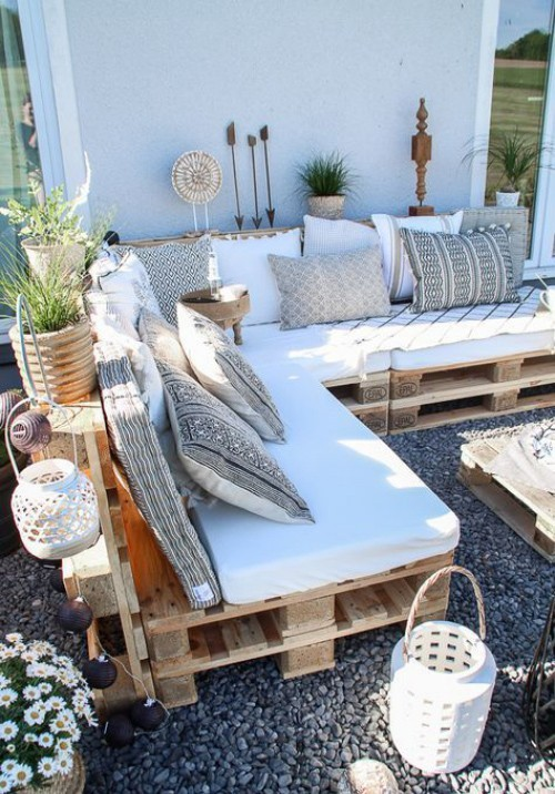 backyard corner, pebbles stones, crate bench with white cuhion, pillows, plants, crate coffee table, basket lamps