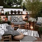 Backyard Corner, Rugs, Rattan Ottoman, Crate Bench With Cushions, Pillows, Wooden Wide Table, Lamps, Plants