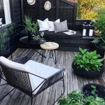 Backyard Corner, Wooden Floor, Black Wooden Bench Near The Fence, Nesting Table, Pillows, Black Round Pots, Black Wooden Cage, Black Wire Chair With White Cushion