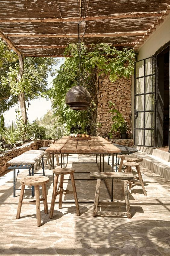 backyard, natural stone floor tiles, wooden table, wooden stools, metal bench, pendants, rattan roof