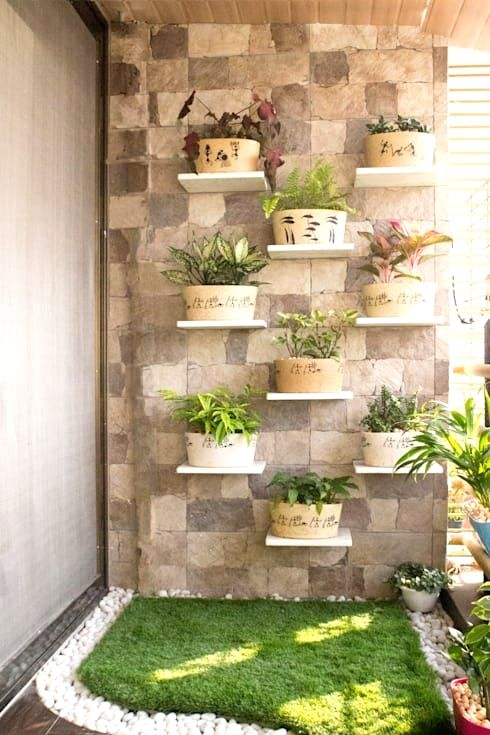 balcony with cornered garden, grass, white pebbles, stone wall, floating white small shelves with pots