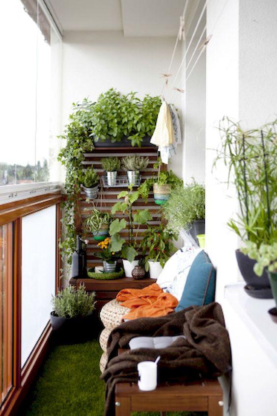 balcony with grazz floor, wooden planks, vertical pots plants. wooden bemch, rattan ottoman