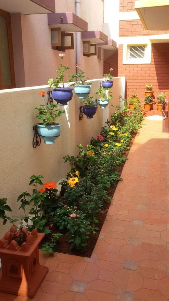 balcony with orange floor tiles, plants on soil floor, floating pots with detailed metal hooks