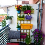Balcony With Wooden Floor, Rattan Table And Chair, Colorful Pots Hooked On The Wooden Frame With Plants