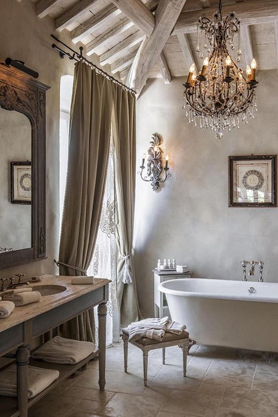 bathroom, beige wall, beige floor tiles, white tub, white wooden cabinet, white wooden stool, crystal chandelier, opened wooden ceiling, antique sconces, curtain, mirrror