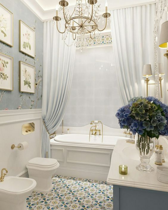bathroom, blue pattern floor tiles, blue flower wallpaper, white wainscoting, white tub, blue grey cabinet, white sink, white wall tiles, white curtain, chandelier, white toilet