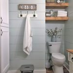 Bathroom, Brown Floor Tiles, Off White Wall Plank, White Toilet, Wooden Floating Shelves Above Toilet, White Vanitu With Wooden Top, White Clothes Hook
