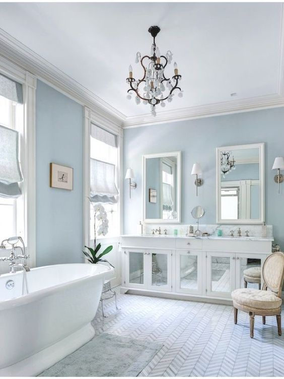 bathroom, chevron floor tiles, grey ryg, white tub, white wooden cabinet with mirror door, white vanity sink, white chandelier, blue wall, roman shade, beige chair