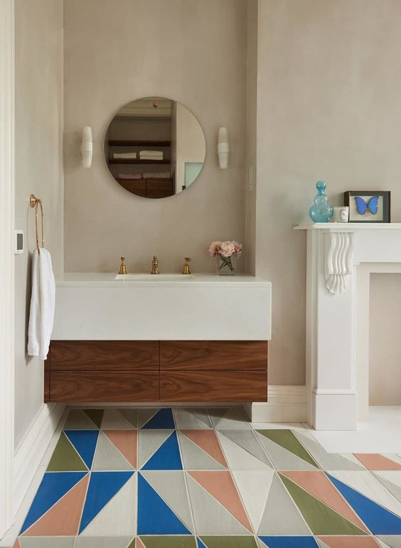 bathroom, floating vanity with wooden drawers, white top and sink, round mirror, sconce, white fireplace, colorful floor tiles in geometric
