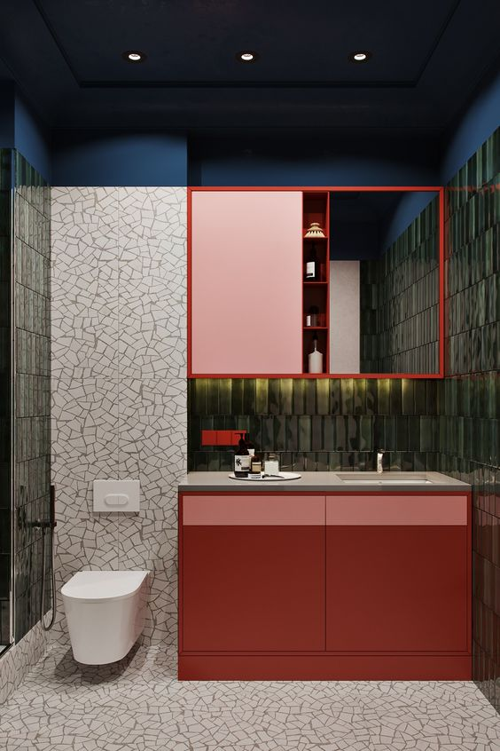 bathroom, green tiles on the wall, red cabinet, white marble top, red upper cabinet, mirror, white marble cuts tiles, white floating toilet