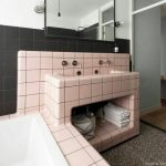Bathroom, Grey Floor, Pink Square Tiles On The Vanity And Sink Continued To The Tub With White Inside, Black Square Half Wall, White Wall, Bulbs Sconces, Mirror