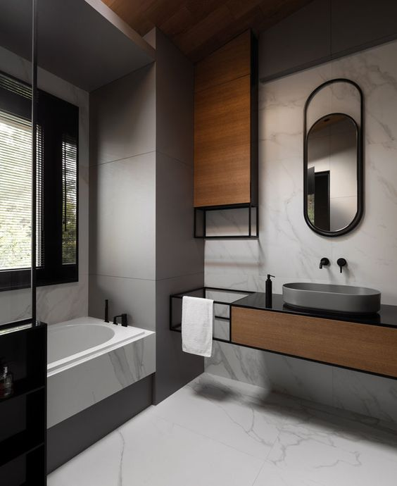 bathroom, marble floor and wall, grey wall,  marble tub with grey paint under, floating vanity with wooden and black metal, black top, grey sink, mirror