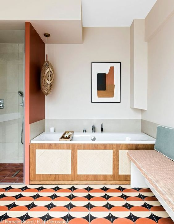 bathroom, pattern floor tiles, tiles bench, wooden tub with white inside, beige wall, orange partition,