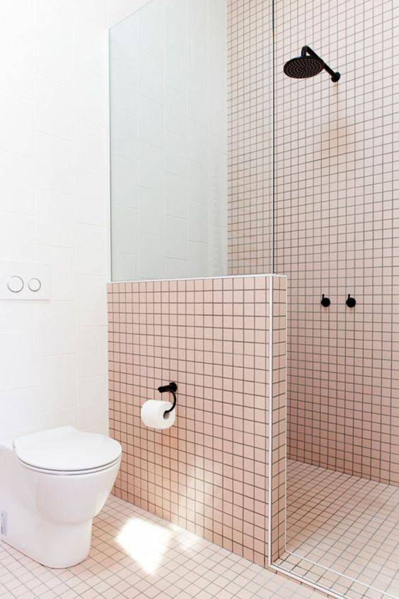 bathroom, pink tiny square tiles on the wall, floor, partition with glass, white toilet, white wall