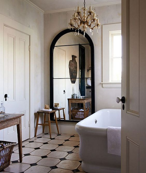 bathroom, white black tiles, white wall, crystal chandelier, white tub, windows, wooden table, wooden stool
