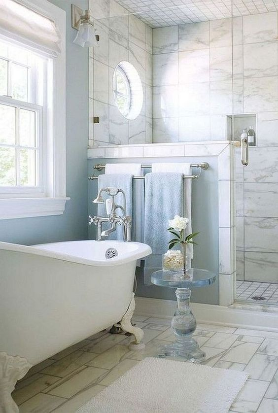 bathroom, white floor tiles, white marble wall tiles, white tub with crook, towel holder, white sconces, windows