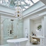 Bathroom, White Marble Floor Tiles, White Tub, Clear Glass Partition, White Chandelier, Clear Glass Roof, White Cabinet And Vanity Table With White Golden Chair