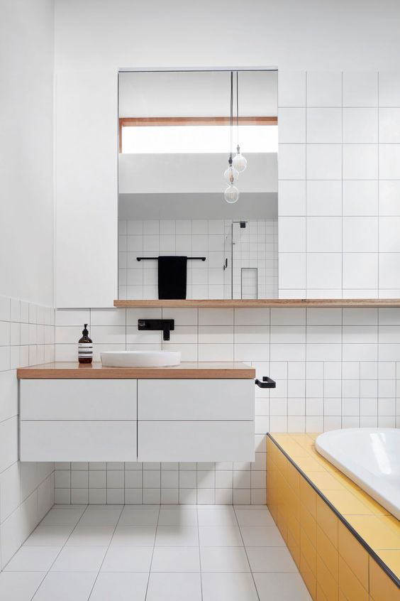 bathroom, white square tiles in different size in the floor, wall above the shelves and under, floating white vanity, wooden top, white round sink, yellow tiles tub, white tub