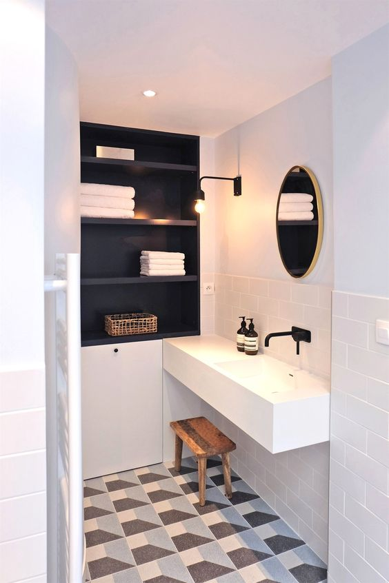 bathroom, white subway wall tiles, white floating sink, round mirror, black built in shelves, patterned tiles