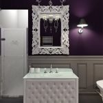 Bathroom, White Wainscoting, Purple Wall, White Molding Ceiling, White Tiles Floor, White Tufted Cabinet With White Top And Sink, Vintage White Framed Mirror, Chandelier