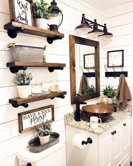 bathroom, white wall plank, wooden floating shelves, white toilet, wooden framed mirror, copper sink, white cabinet, sconces