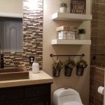 Bathroom With Brown Tiles, Brown Backsplash, Beige Wall, White Toilet, White Floating Shelves, Beige Vanity Top With Brown Sink, Dark Brown Vanity, Mirror, Sconce