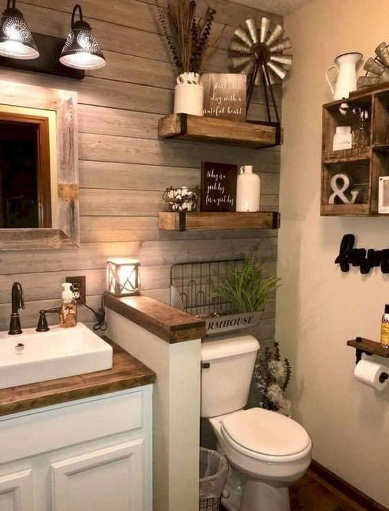 bathroom with wooden floor, white toilet, white wooden cabinet, wooden top, white sink, wooden plank wall, white wall, floating shelves, wooden framed mirror, sconces